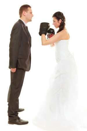 Conflict in relationship concept. Married couple fighting with each other. Woman wearing wedding dress and boxing gloves punching her husband in elegant suit. photo