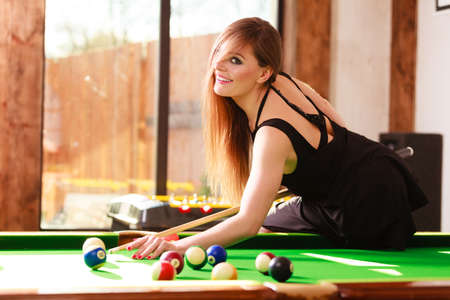 Play and fun concept. Young happy girl having fun with billiard. Smiling fashionable woman playing spending time on recreation.