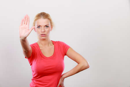 Refusal, denial signs. Blonde woman showing stop gesture with open hand, refusing something. Stock Photo
