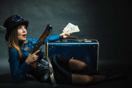 flintlock: Fashionable subculture weapon concept. Steampunk girl with cash. Young gorgeous lady in victorian fashion lying on floor with banknotes briefcase and blunderbuss. Editorial