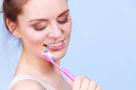 whiten: Woman brushing cleaning teeth. Girl with toothbrush. Oral hygiene. Blue background