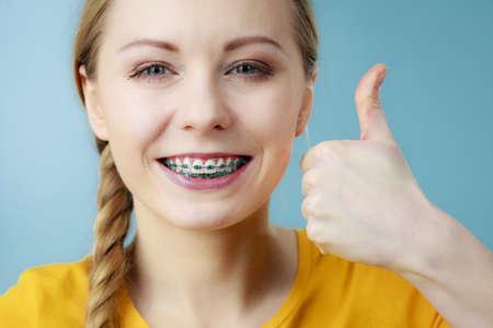 歯科医や歯科矯正医の概念。若い女性 10 代笑っている女の子を中かっこ、歯を見せブルーの手の手話を親指を作る 報道画像