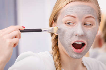 Skincare. Young funny woman applying with brush grey clay mud mask to her face. Female taking care of skin condition. Spa beauty treatment.