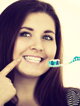 whiten: Woman holding toothbrush with paste on it. Smiling positive girl ready to cleaning teeth. Oral hygiene. IFiltered photo
