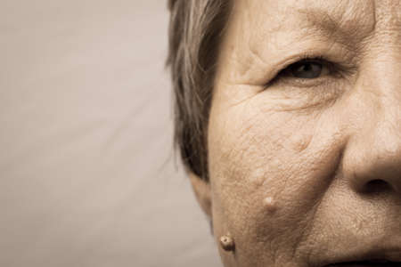Details of senior woman half face. Elderly pensioner female, cheek and eye close up. Stock Photo