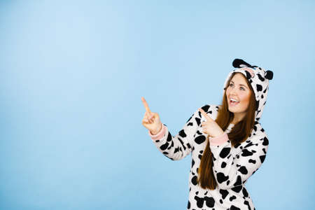 People dressed up like animals concept. Happy crazy woman in funny cow pajamas costume pointing at copyspace.