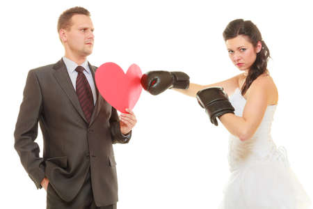 Conflict in relationship concept. Married couple fighting with each other. Woman wearing wedding dress and boxing gloves punching her husband in suit holding heart. photo