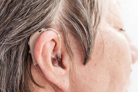amplify: Closeup senior woman with hearing aid in her ear. Health care, hear amplify, device for the deaf. Stock Photo