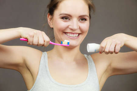 whiten: Woman holding toothbrush and placing toothpaste on it. Dental health care. Dark black background