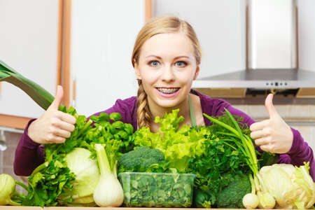 Woman in kitchen with many green leafy vegetables making thumb up hand sign gesture.