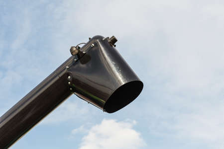 Black chute or drainpipe with sky in background Stock Photo