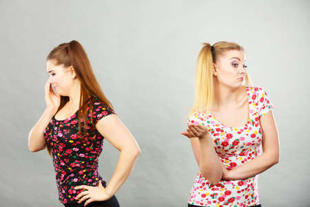 Two young women being offended by each other, got the hump and standing backwards
