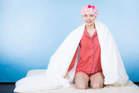 woman bath: Funny happy woman after shower wearing pink pajamas and dotted bathing cap sitting on bed covered with white fresh blanket.