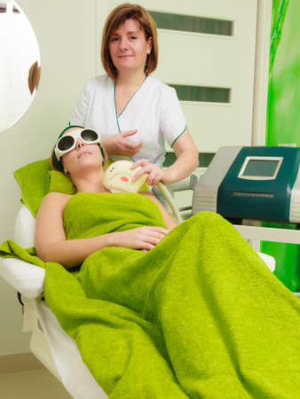 Medical cosmetology, modern cosmetic devices concept. Woman wearing safety glasses, getting laser treatment on her cleavage in beautician