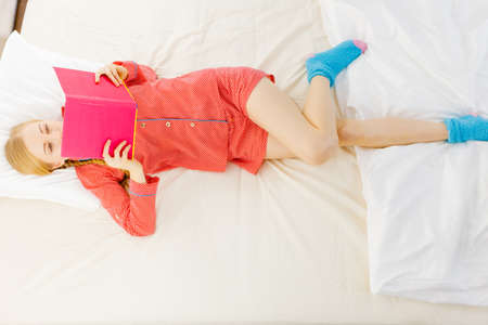 Girl lying in bed reading book. Young blonde female wearing red dotted pajamas relaxing at home on mattress. Top view