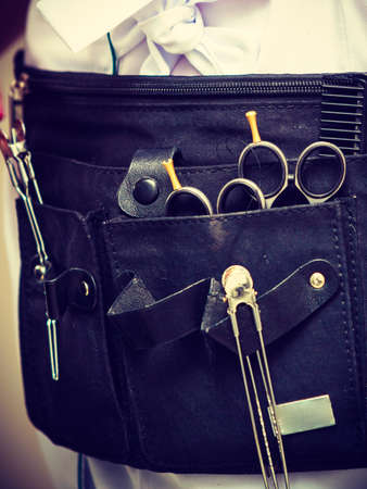 Hairdressing equipment concept. Professional hairdresser tools in black belt. Scissors, combs and clips.