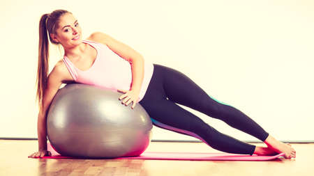 Sport exercises workout health concept. Tired girl resting. Exhausted lady catching a breath after exercising with fitness ball.