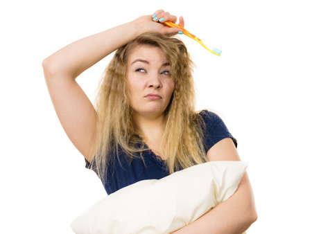 Mujer soñolienta con el pelo enredado rubia abrazando la almohadilla blanca sosteniendo el cepillo de dientes que se siente cansado o resaca. Estudio, tiro, aislado Foto de archivo - 81880916