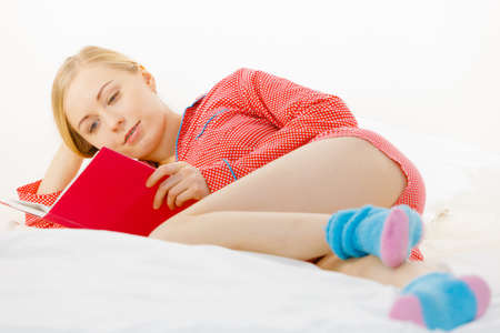 Girl lying in bed reading book. Young blonde female wearing red dotted pajamas relaxing at home on mattress. Фото со стока