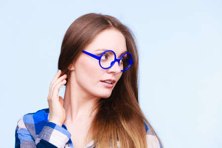 Studying, beauty of education and fun concept. Attractive nerdy woman in weird big glasses. Studio shot on blue background