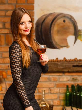 degustation: Elegant beauty lady long hair full make up wearing black dress tasting wine in rural cottage interior celler