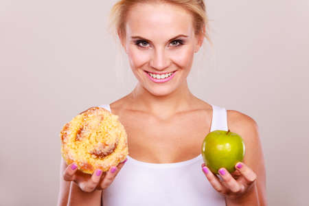 Woman holds in hand cake sweet bun and apple fruit choosing, trying to resist temptation, make the right dietary choice. Weight loss diet dilemma concept. Stock Photo