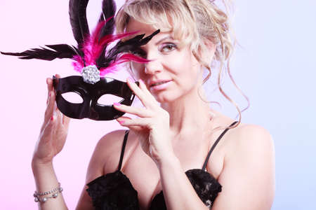 Party time, holidays, people and celebration concept. Woman middle aged blonde female holds carnival mask. Lady wearing elegant black dress