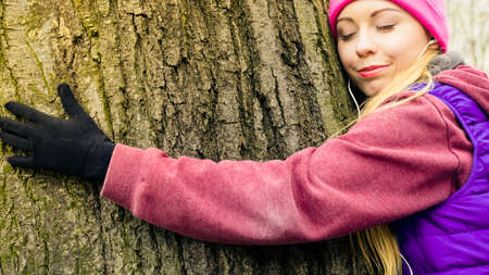 environmentalist: Woman wearing sportswear giving hug embracing tree trunk being in love with nature.