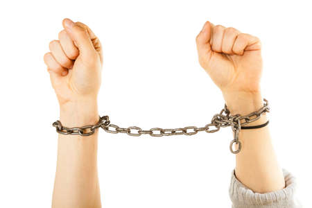 Lack of freedom, social problems concept. Chained man hands with chain around wrists Stock Photo