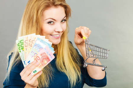 Economy, buying things, customer concept. Happy smiling woman holding shopping cart with euro money inside