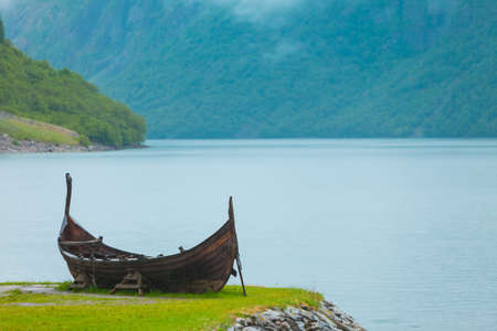 Old wooden viking boat on seashore in norwegian nature, foggy misty day. Mountains and fjord Sognefjord. Tourism and traveling concept Stock Photo
