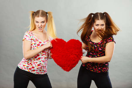 Two agressive young teenage women having argue fighting, pulling heart shaped pillow. Female violance concept.