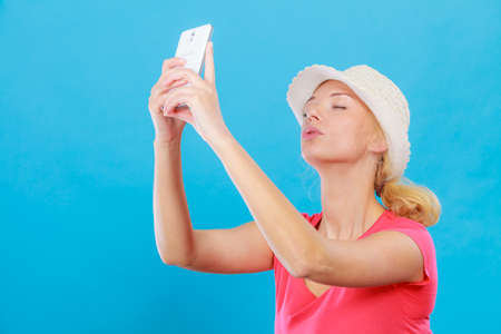 Technology, modern photography, confidence conept. Happy attractive adult blonde woman in sun hat taking picture of herself with smartphone, selfie.