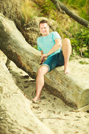 Summertime relaxation, vacation and holiday, adventure traveling concept. Handsome man sitting on tree trunk relaxing during summer. photo