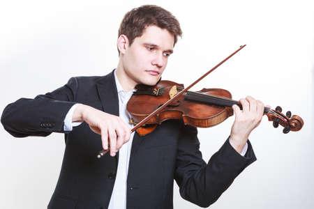 音楽への情熱、趣味概念。若い男は、エレガントな木製のバイオリン演奏を着ています。白い背景で撮影スタジオ