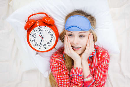 ショックを受けた若い女性が遅刻時間を示す大きな赤い昔ながらの時計を保持しているかわいいピンクのパジャマを着てします。 写真素材