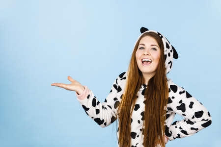 Happy teenage girl in funny nightclothes, pajamas cartoon style presenting something, holding open empty hand with positive face expression, studio shot on blue. Advertisement concept.