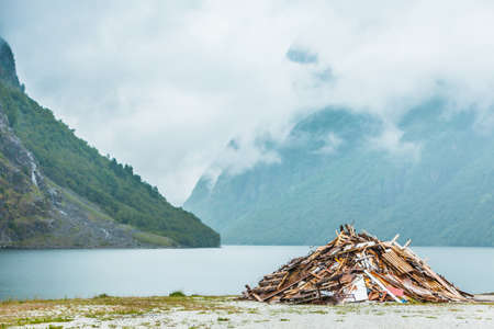 Tourism travel and making earth clean concept. Pile of garbage on seashore. Mountains and fjord in Norway, Scandinavia. Misty foggy day