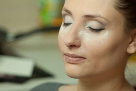 Visage, cosmetics concept. Woman with full make up closeup, powder dust on cheeks, baking method