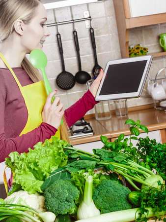 Young woman in kitchen having many green vegetables on table, holding tablet thinking about cooking something and searching for recipes in internet Editorial