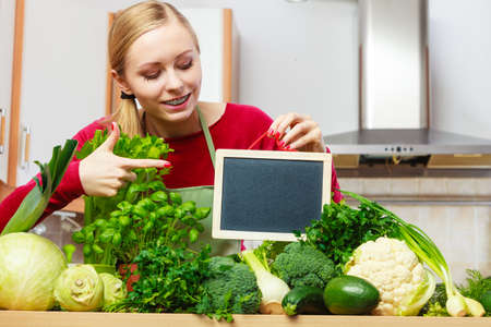 Young woman in kitchen having many green vegetables about to cook something healthy and vegetarian, holding blank black board for copyspace Editorial