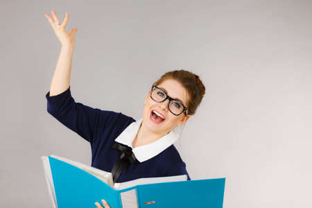 Happy positive accountant business woman holding binder with documents, enjoying her work finding great problem solution.