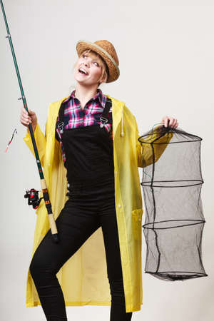 Spinning, angling, cheerful fisherwoman concept. Happy woman in yellow raincoat holding fishing rod and keepnet having fun. Stock Photo