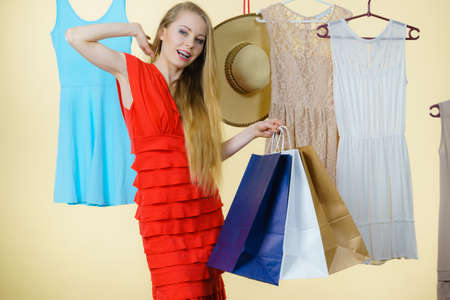clothing store: Woman in clothes shop store holding shopping bags picking summer perfect outfit, dress hanging on clothing hangers