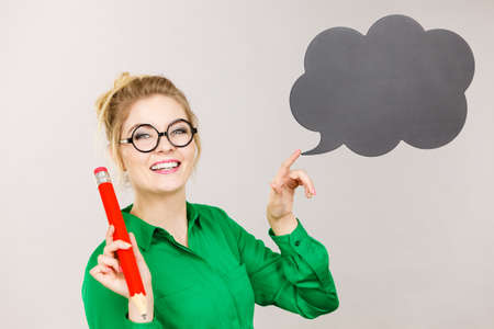 oversized: Student looking woman wearing nerdy eyeglasses holding big oversized pencil thinking about something, black speech bubble next to her Stock Photo