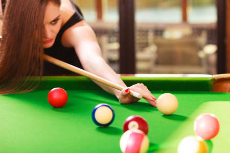 billiard: Competition concept. Young focused girl having fun with billiard. Pretty fashionable woman spending time on playing rivalry. Stock Photo
