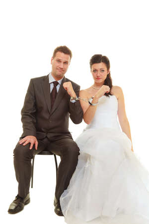 Couple problems, love forever concept. Bride and groom in handcuffs wearing wedding outfits photo