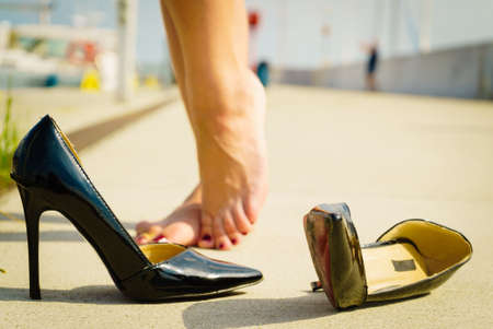 Moda e calzature. Pattini classici neri dell'alto tallone durante la giornata di sole, i piedi della donna sentono dolore Archivio Fotografico - 82568651