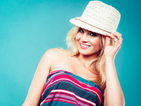 Summer trendy fashionable outfit ideas concept. Blonde woman wearing colorful striped strapless shirt and white fedora hat Stock Photo