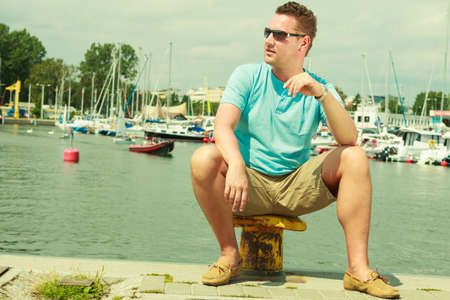Summertime vacation adventure concept. Man spending his free time walking on marina, sightseeing during summer, guy sitting on bitt. photo
